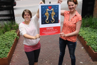 Maartje en Sandra met de aankondigingsposter van de expo Tekst Getekend. Fotografie Romy van der Sande.